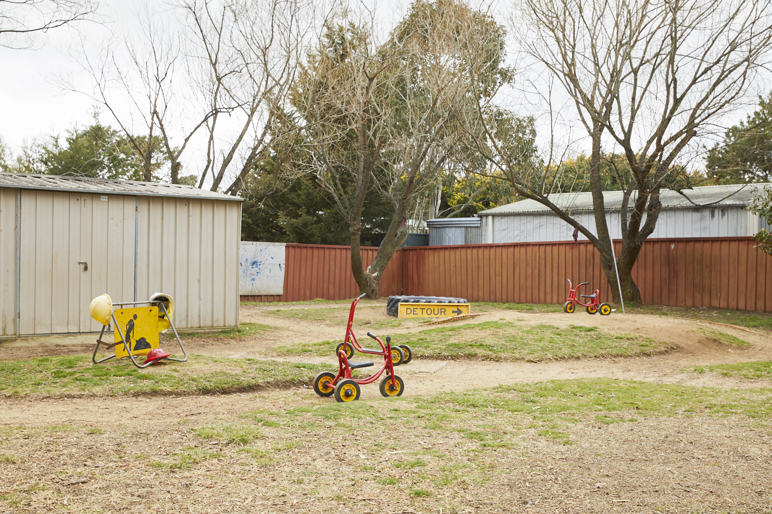 Child on bike in outdoor play area at Milestones Bungendore